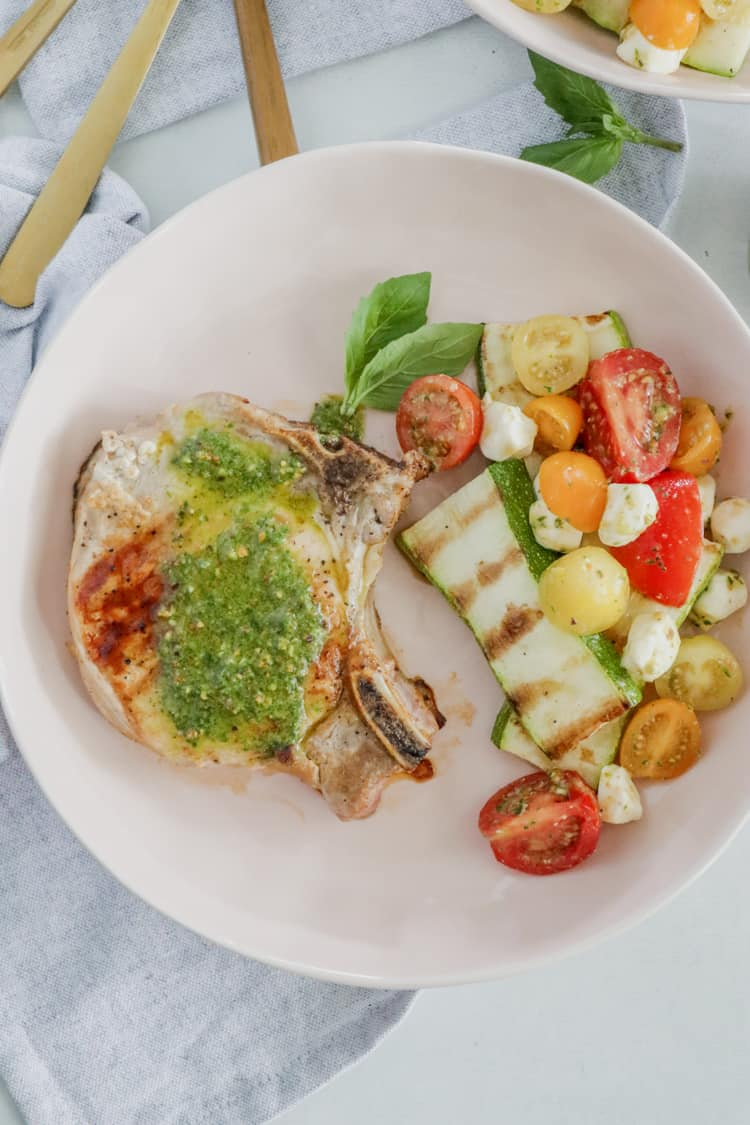 Pesto Grilled Pork Chops! Juicy grilled pork chops topped with a fresh and flavorful pesto sauce are ready to enjoy in under 30 minutes; this dinner tastes like the perfect summer meal!