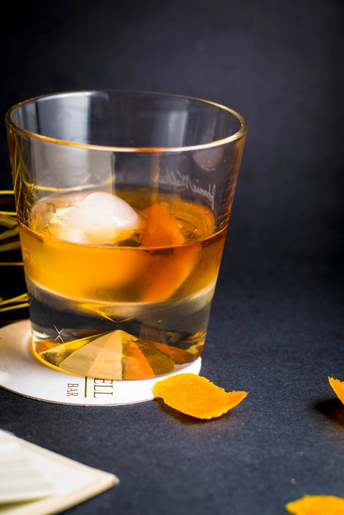 Cocktail on table with orange peels