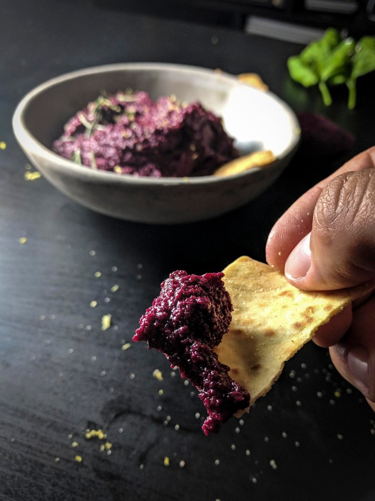 Close up of beet hummus on pita chip with bowl in background