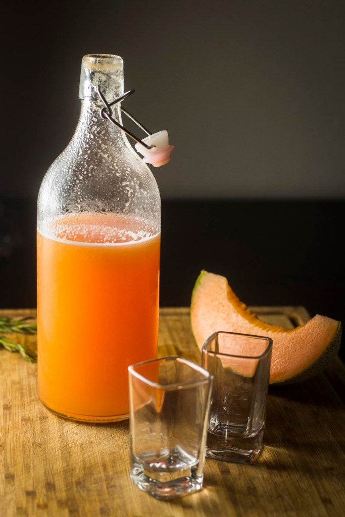 Meloncello bottle on board with sliced melon and shot glasses