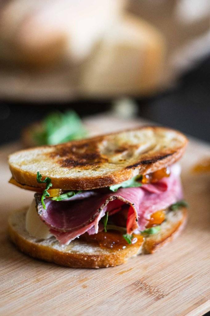 sandwich with orange marmalade on cutting board
