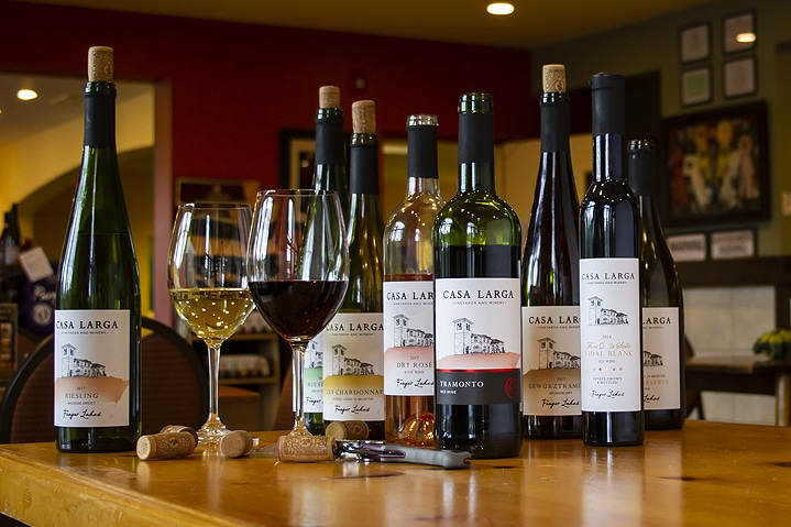 Collection of Casa Larga Vineyards wines with filled wine glasses and wine corks at Casa Larga Vineyards