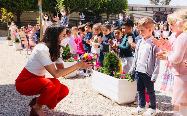 Doña Letizia conversa con uno de los alumnos que le ha ofrecido un ramo de flores