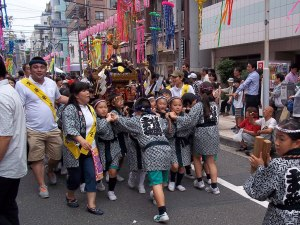 A group of kids carry a mikoshi (shrine float) down the parade route.