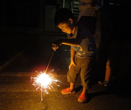 Boy lighting sparklers in the streets of our Japan neighborhood