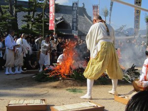 Monks throw thousands of wooden prayer sticks into a blazing fire. In a few minutes, they'll run through the flames.