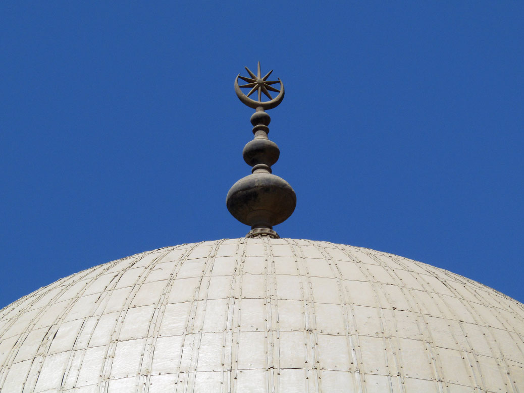 The crescent moon and star, symbol of Islam, sits on top of one of the white domes.