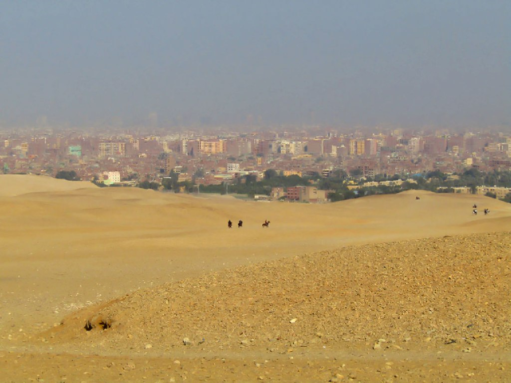 View of desert riders and the city of Cairo in the distance.