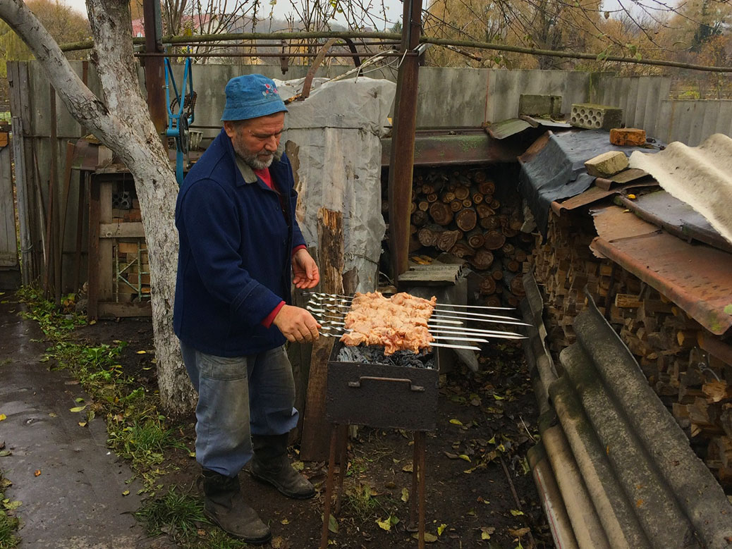 My uncle grilling some pork skewers.