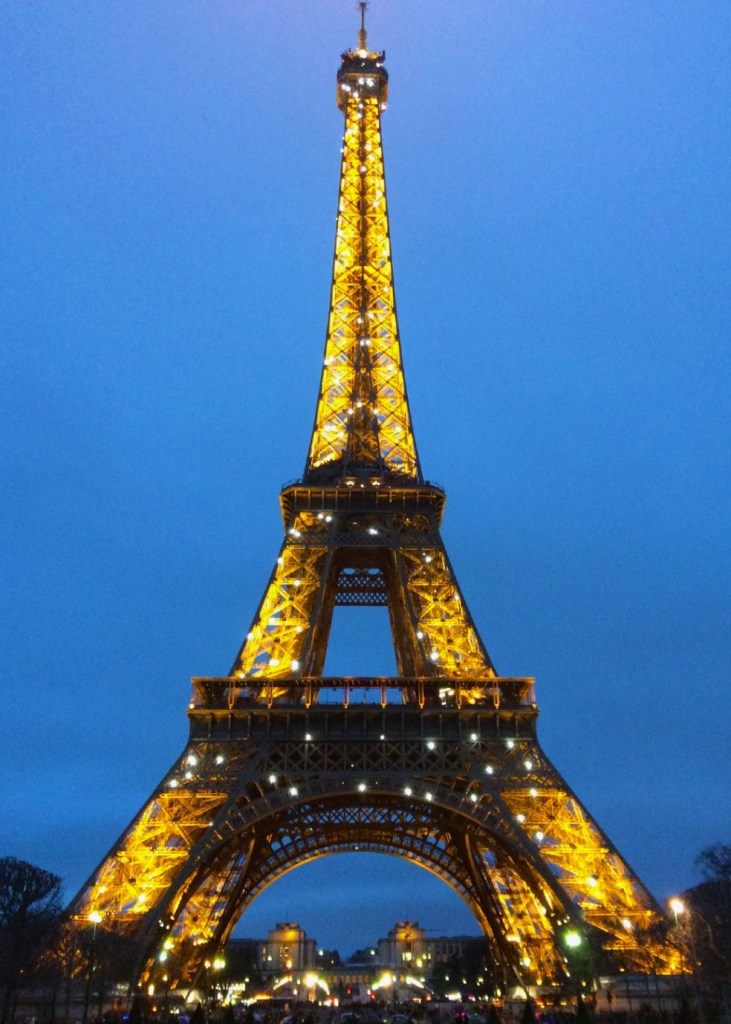 The Eiffel Tower glittering at night as seen from Champ de Mars.