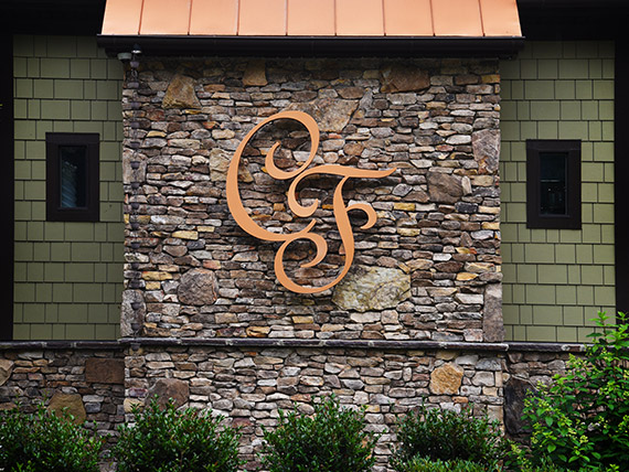Letters C and F in a script font created in metal with a copper look
