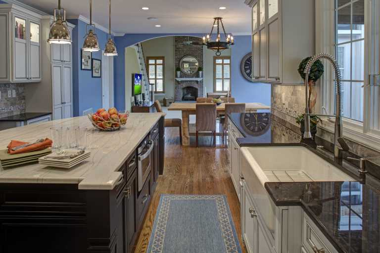 view into dining and living rooms from renovated kitchen traditional style pendant lighting over island