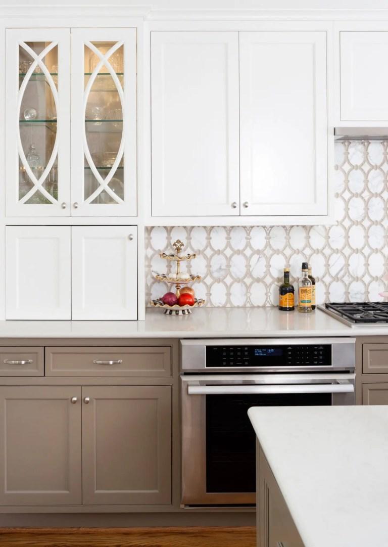 neutral color palette kitchen upper cabinets with glass door design stainless steel appliances geometric backsplash tile