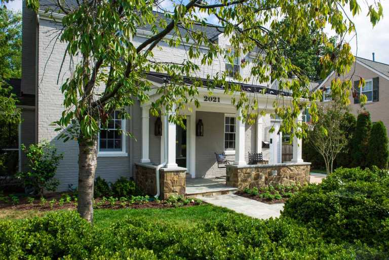 overview of front porch addition traditional farmhouse style stone and lush greenery