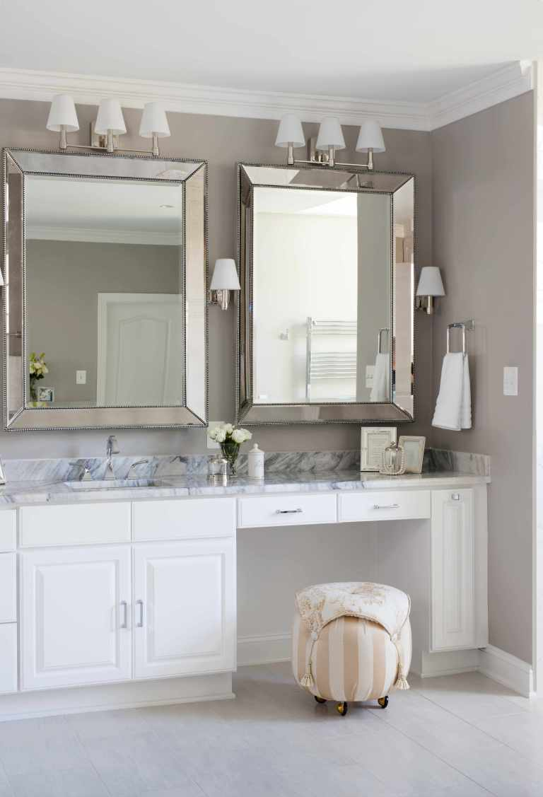 renovated bathroom neutral beige walls white cabinet vanity with built in makeup area sconce lighting crown molding