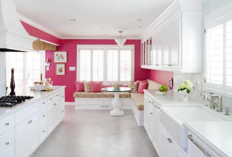 bright white kitchen with hot pink feature wall eat in area with banquette seating