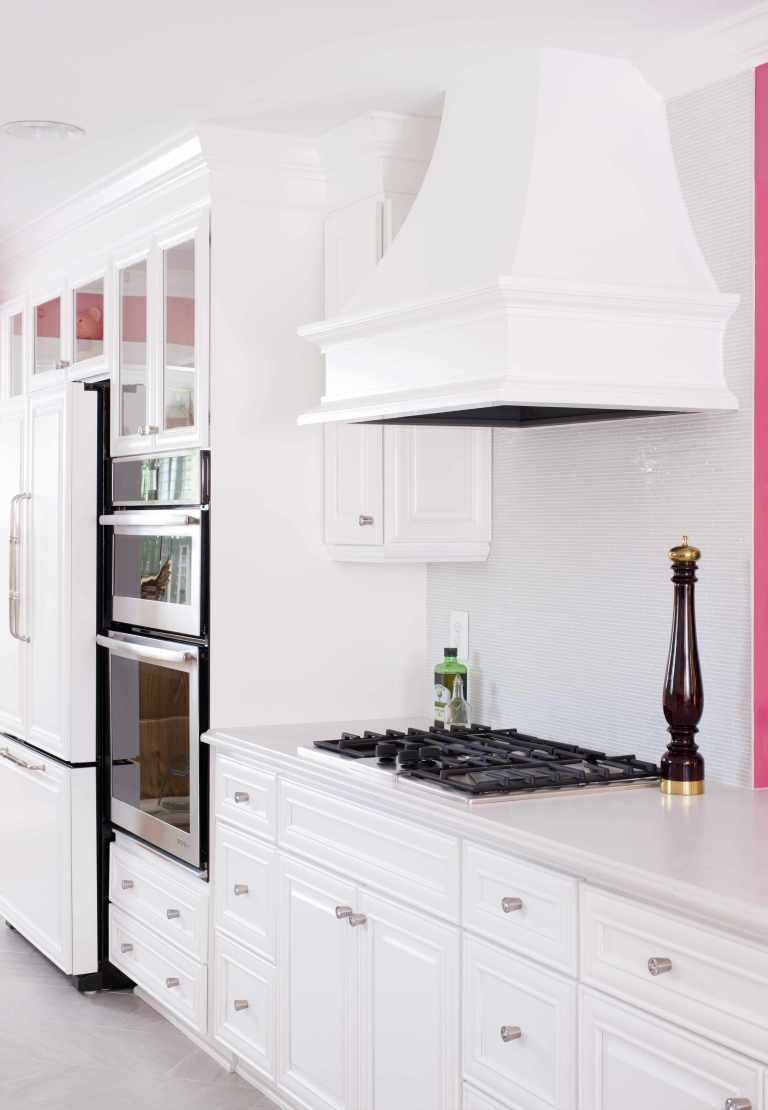white kitchen with hot pink walls gas stovetop and range hood stainless steel appliances wall oven
