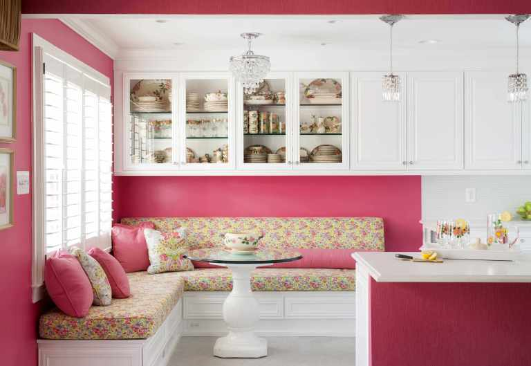 eat in area of kitchen hot pink walls banquette seating upper cabinetry with glass doors