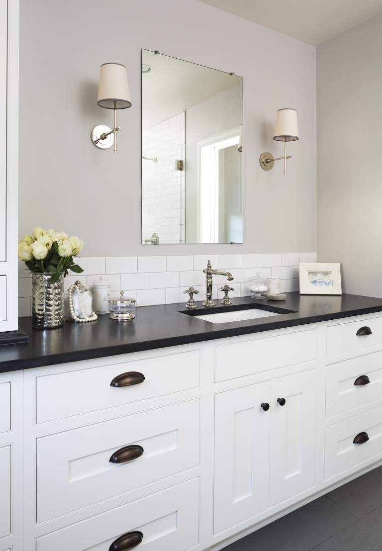 traditional bathroom white cabinets black floor and counter tops sconce lighting