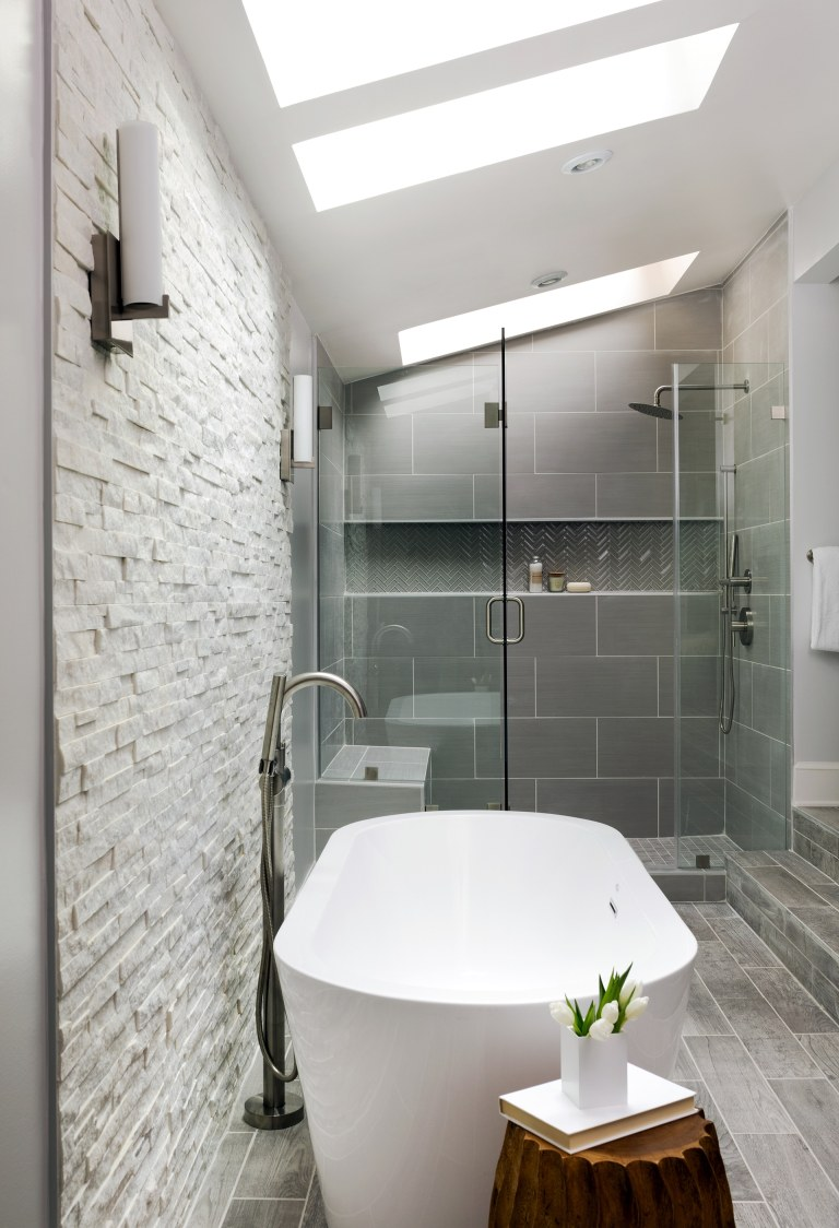 modern bathroom gray color palette separate tub and shower stall with glass door textured stone feature wall skylight