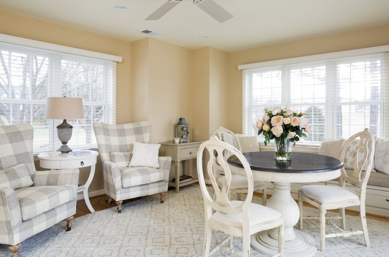 living area soft yellow color palette large windows built in window seat