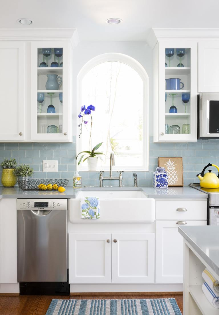 traditional kitchen light blue color palette white cabinetry with glass door uppers farmhouse sink arched window mini stainless steel dishwasher