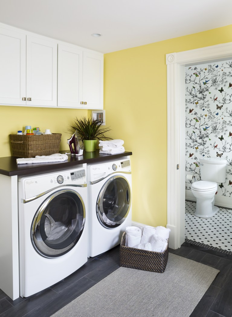 yellow laundry room white cabinetry wood floors plenty of storage