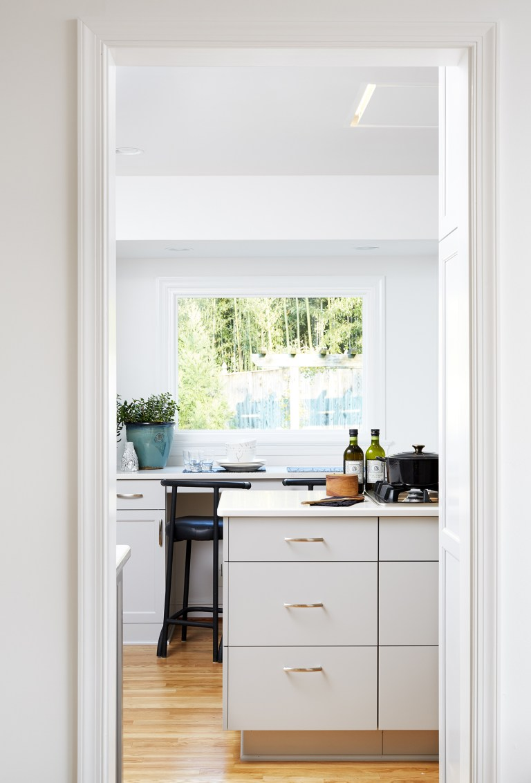 view into kitchen white cabinetry wood floors large window