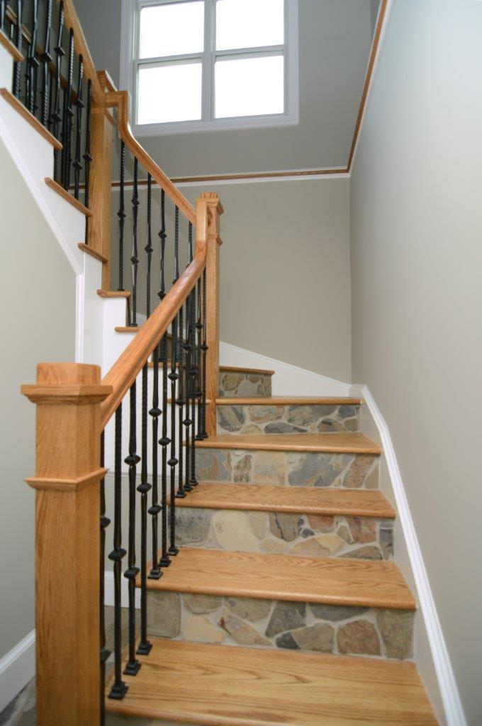 staircase with light wood banister and treads stone risers