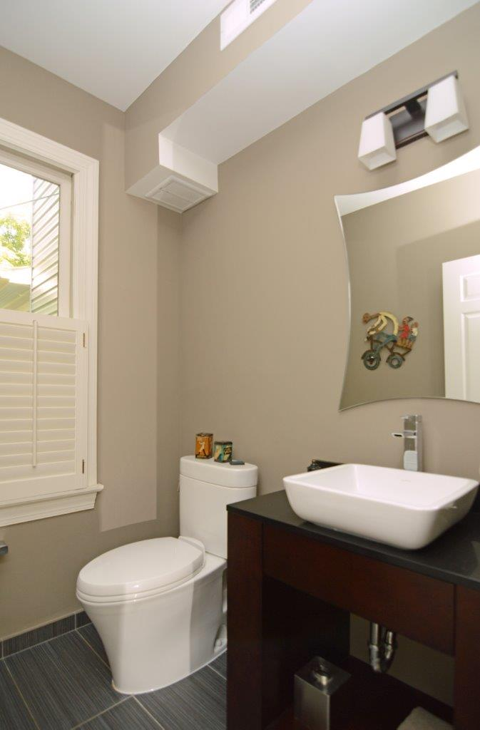 beige bathroom with square basin sink and sconce lighting