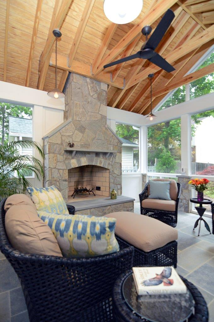 screened in porch addition with stone fireplace and wood ceiling with beams flagstone floors