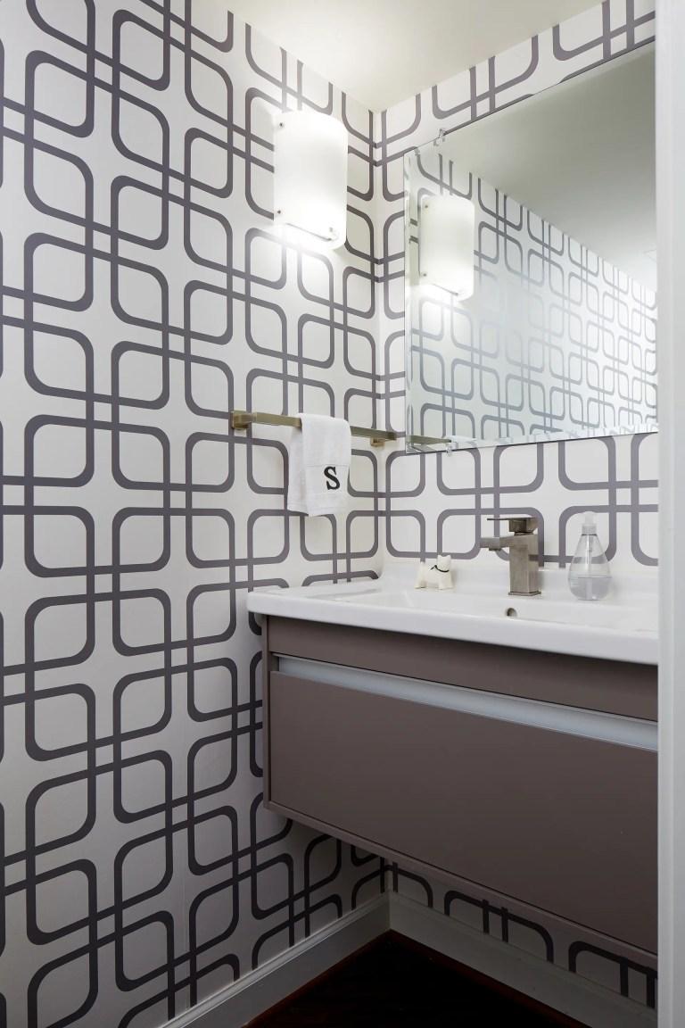 bathroom sink with floating vanity and geometric wallpaper