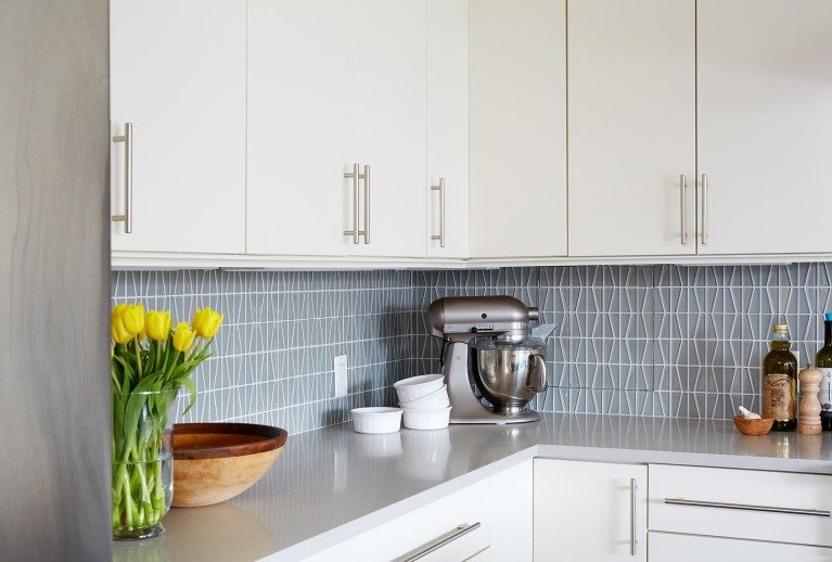 kitchen with white cabinetry gray countertops geometric tile backsplash