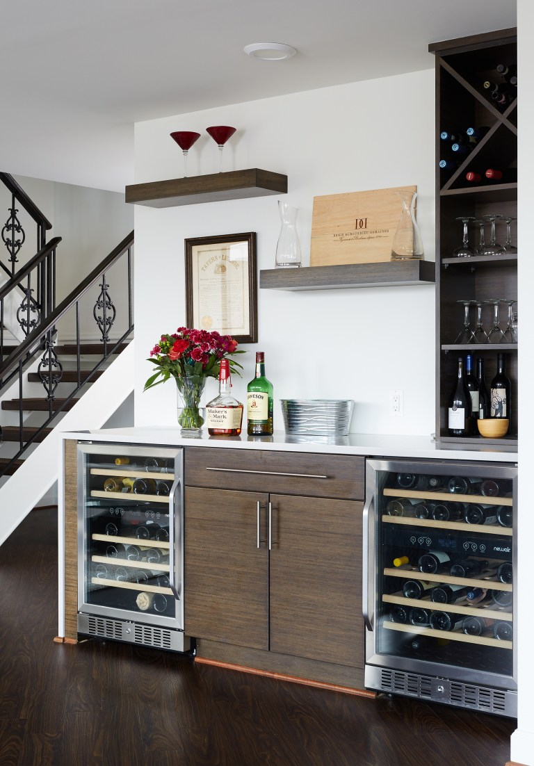 minibar area with dual beverage refrigerators wine storage and floating shelves