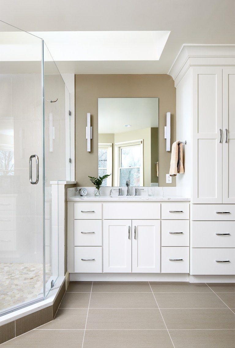 master bathroom shower and vanity with white floor to ceiling cabinetry sky light and sconce lighting