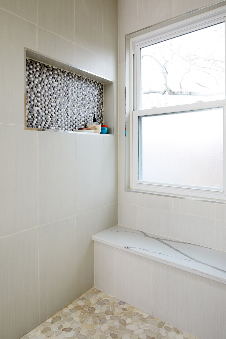 wall nook in shower with mosaic accent tile built in bench and frosted glass window