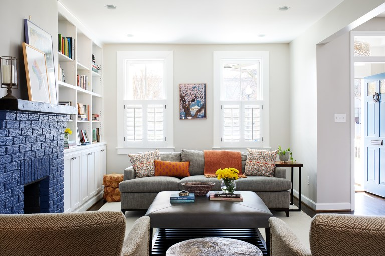 bright living area with built in bookcases and brick fireplace painted blue