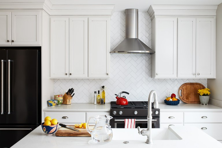 kitchen with white cabinetry and island diamond tile backsplash and black stainless appliances