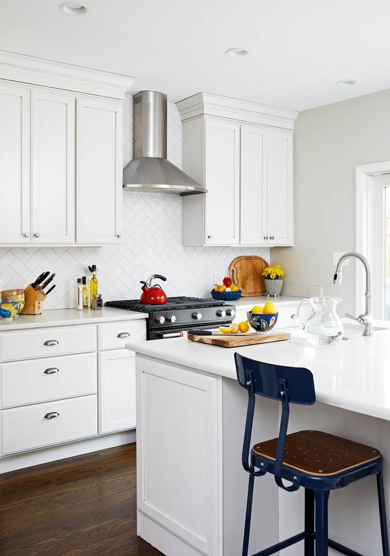 kitchen with dark wood floors and white cabinetry island with seating