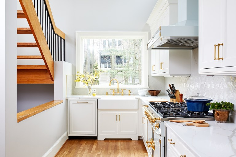 small statement kitchen bright white with gold accents porcelain farmhouse sink wood floors