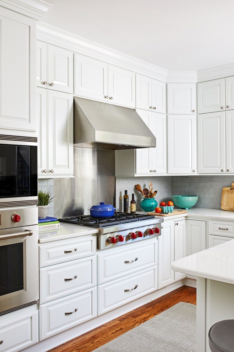 white kitchen with wood floors and stainless steel appliances