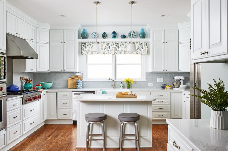 kitchen with white cabinetry wood floors and soft blue color palette island with seating