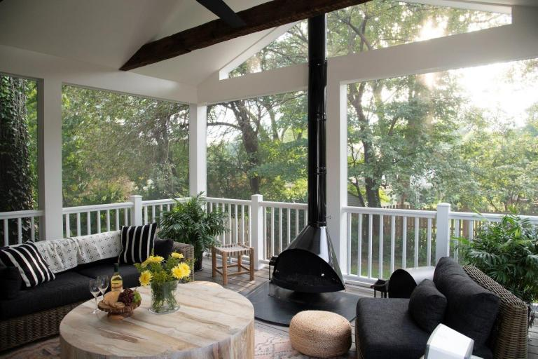 interior design outdoor patio with round wood table and black fire place, black cushion chairs screen porch