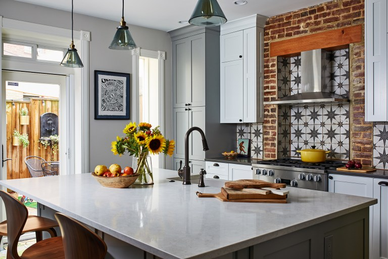 dc design kitchen island with sink and seating with white cabinets with round black knobs