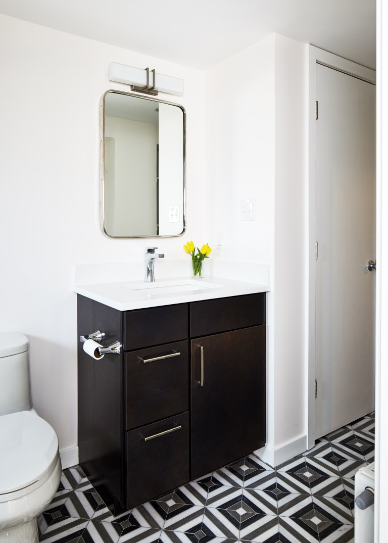 Black and white floor tiles with single sink vanity with mirror