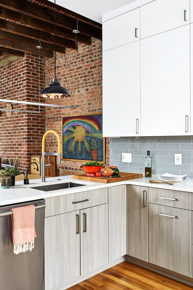 kitchen with gray lower cabinets and white upper cabinets stainless steel appliances peninsula with sink open to dining area with exposed brick and wood beams