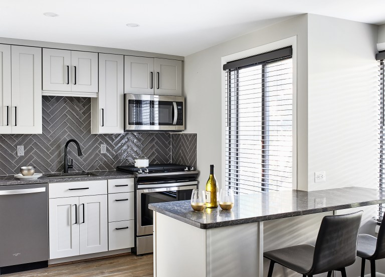 transitional gourmet white and grey kitchen with subway grey backsplash, black faucet