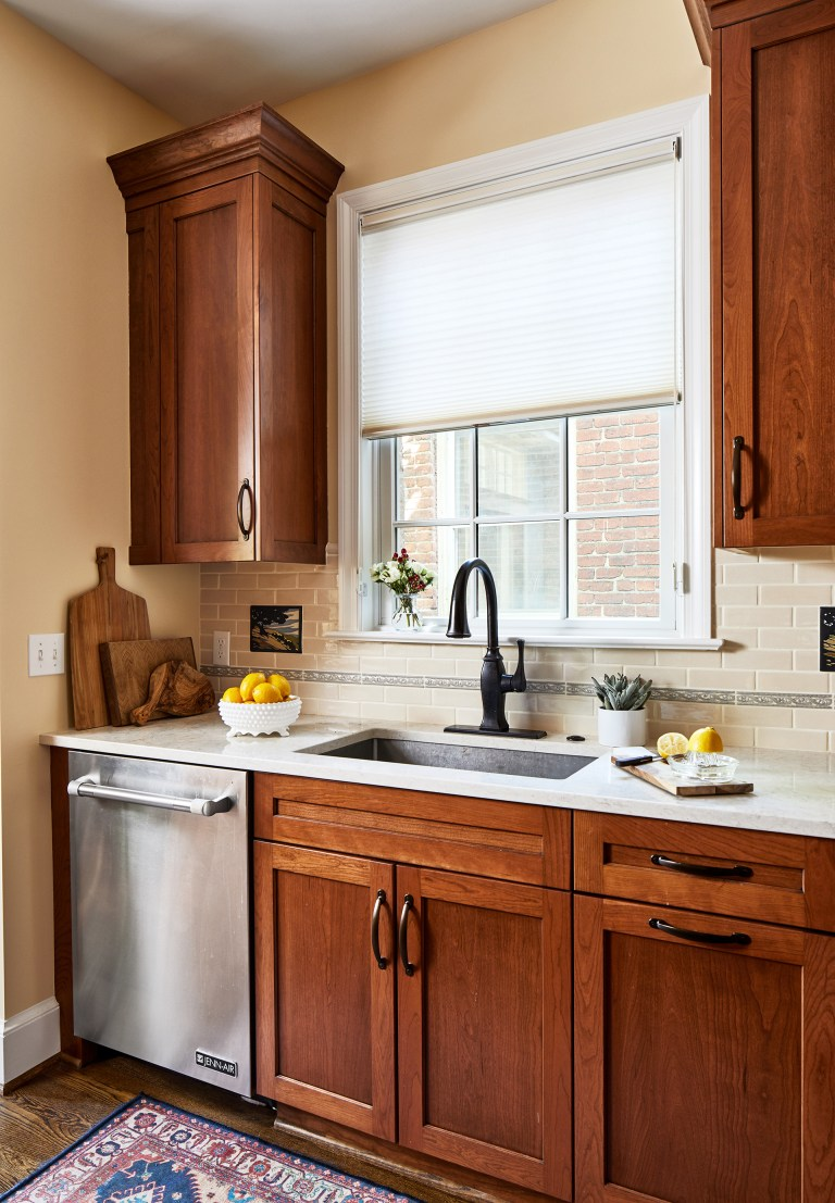 tall wood floating kitchen cabinets with farmhouse sink and window view, stainless steel dishwasher