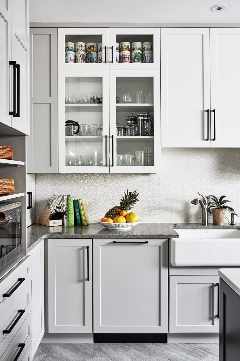 transitional kitchen with white glass cabinets with black pull handles