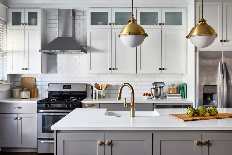 white marble top kitchen island with gold faucets and white opal brass two-light pendant with frosted glass above kitchen island